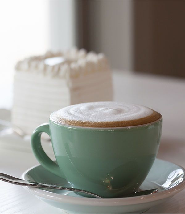 Hot cappuccino and cake on the table.